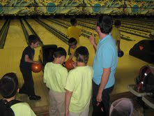 Young kids learning how to bowl and having a good time